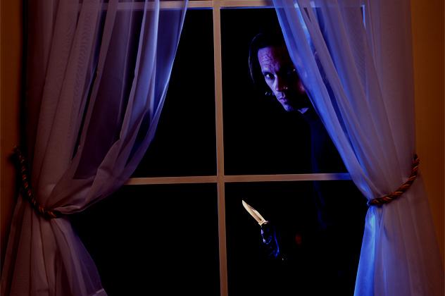 Portrait of a thief peeking through a window